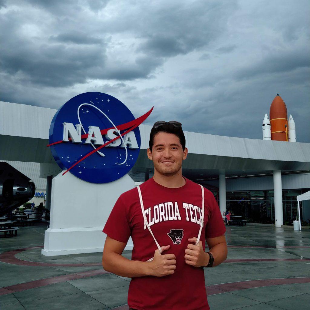 Luiz Fernando com a camisa da Florida Tech na frente  da base da NASA: o jovem sonha com a oportunidade de trabalhar ou conduzir pesquisa na agência espacial